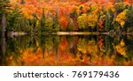Fall colour reflected in the still waters of Canisbay Lake, Algonquin Provincial Park, Ontario, Canada - stock photo