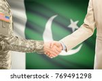 Small photo of American soldier in uniform and civil man in suit shaking hands with adequate national flag on background - Pakistan