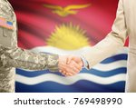 Small photo of American soldier in uniform and civil man in suit shaking hands with adequate national flag on background - Kiribati