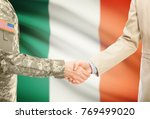 Small photo of American soldier in uniform and civil man in suit shaking hands with adequate national flag on background - Ireland