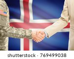 Small photo of American soldier in uniform and civil man in suit shaking hands with adequate national flag on background - Iceland