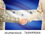 Small photo of American soldier in uniform and civil man in suit shaking hands with adequate national flag on background - Honduras