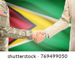 Small photo of American soldier in uniform and civil man in suit shaking hands with adequate national flag on background - Guyana
