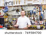 smiling young man cashier... | Shutterstock . vector #769584700