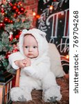 Small photo of Cute babe in a white blouse sitting next to the Christmas tree the Christmas tree