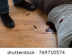 Small photo of murder, kill and people concept - criminal or murderer with bleeding dead woman body lying on floor and bullet sleeves at crime scene (staged photo)