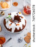 Small photo of Traditional christmas cake with dried fruits soaked in rum and sugar glaze. Teatime with heart-shaped ginger cookies. Christmas background with festive decoration.