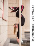 Small photo of A young, slender girl in tight black tracksuit, doing complex acrobatics in the street in cloudy weather. Very good stretching and flexible back.