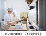 smiling cooks work in the bakery | Shutterstock . vector #769854988