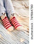 feet in wool socks at fireplace.... | Shutterstock . vector #769864780