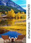 """Small photo of """"Indian summer"""" in Rocky Mountains of Canada. Two comfortable loungers by the Abraham lake with turquoise water. Concept of ecological and active tourism"""