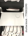Small photo of The white table tray and seatbelt are set in the passenger seat in airplane for convenience and safety in every flights.