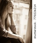 Small photo of People and solitude concept. Alone sad young woman long hair teen girl sitting on window sill lost in thought, urban city in the background