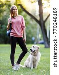 Stock photo picture of young girl on walk with dog in summer 770248189