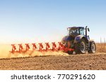 Small photo of Agriculture. The tractor prepares the ground for sowing and cultivation. Agronomy, the concept of farming. Agricultural machinery for fields, Work of a plow on the field
