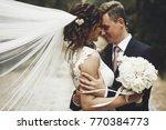 groom hugs bride tender while... | Shutterstock . vector #770384773