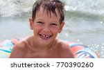Small photo of Boy in inflatable ring floating on the sea all wet and happy