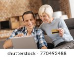 Small photo of Need purchases needed. Pleasant elderly woman holding a bank card, being ready to make online purchase while her adult son helping her