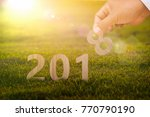 Small photo of Happy New Year 2018. Hand take hold wood placed at warm tone with grass background.