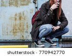 Small photo of Close-up of riotous teenager wearing a jacket and trainers, smoking a cigarette