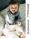 Small photo of Happy toddler holding a tablet in bedroom. Education, gadget, dependency, technology, raising children concept