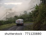 Small photo of Truck collecting routes on rural route between hills in Colombia.