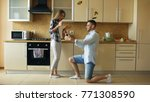 Small photo of Young man making proposal to his girlfriend in the kitchen at home