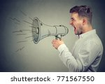 Small photo of Young anxious man shouting with anger posing with painted loudspeaker.