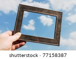 a hand is holding a metal frame against the blue sky - stock photo