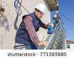 man sanding exterior handrail | Shutterstock . vector #771585880