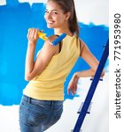 Happy beautiful young woman doing wall painting, standing near ladder - stock photo