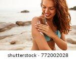 young woman applying sunscreen... | Shutterstock . vector #772002028