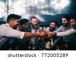 group of young men toasting... | Shutterstock . vector #772005289