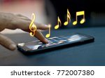 Small photo of Abstract hand playing music notes on smartphone at night background, music concept