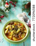 Small photo of Chicken liver and heart (offal) stewed with potatoes and tomatoes on a festive Christmas table.