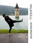 Small photo of Traveler asian thai woman travel and posing for take photo at Submerged tower of reschensee church deep in Resias Lake in Trentino-Alto valley or Alto Adige in Bolzano or bozen city at Italy