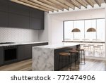 Stock photo side view of a white wooden kitchen with a white marble bar black countertops and a dining room 772474906