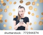 Small photo of Astonished young woman with a ponytail wearing a black T shirt and looking at her smartphone screen with an open mouth. She is standing near a gray wall under a bitcoin rain