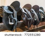 rider leather saddles on fence | Shutterstock . vector #772551280