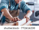 Close-up of male carpenter using sandpaper on a piece of wood for furniture - stock photo