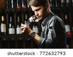 Small photo of Bokal of red wine on background, male sommelier appreciating drink