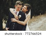 beautiful bride hugs groom from ... | Shutterstock . vector #772766524