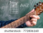 Small photo of Man in a blue denim shirt playing guitar chords displayed on a blackboard, Chord A minor 7