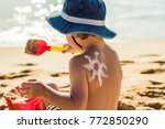 Small photo of The sun drawing sunscreen ,suntan lotion on baby boy back. Caucasian child is sitting with plastic container of sunscreen and toys on sunny beach. Close up, outdoor.
