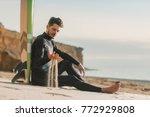 surfer sitting on the beach... | Shutterstock . vector #772929808