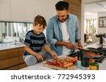 little boy cutting vegetables... | Shutterstock . vector #772945393