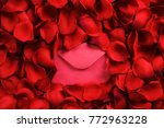 Stock photo red envelope in red rose petals top view valentines day romantic love letter concept 772963228