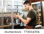 a young guy barista works at... | Shutterstock . vector #773016556