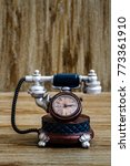 Small photo of Desk clock with antic telephone shape on brown wooden background