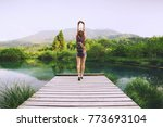 young woman stands on a wooden... | Shutterstock . vector #773693104